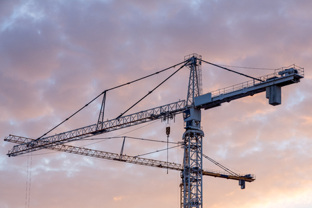 Industrial construction cranes at morning sunrise over the city. Photo taken on October 15, 2018 Banco de Imagens