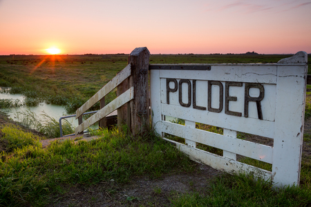 Early sunrise over a dutch polder, near Durgerdam, Amsterdam, the Netherlands. A fenced Sign mentioned the word Polder under a clear colorful sky. Photo taken on September 18, 2018