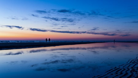 Beach sunset with blue and orange sky with reflections of clouds in a water pool, and silhoutted couple walking, Noordwijk, the Netherlands