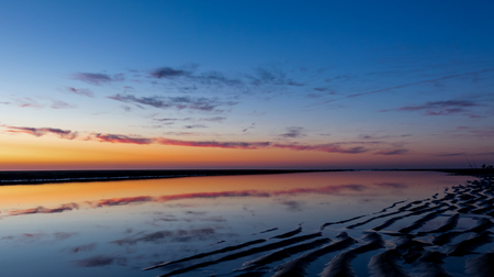 Beach sunset with blue and orange sky with reflections of clouds in a water pool, Noordwijk, the Netherlands Banco de Imagens