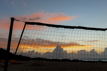 Volleyball net at sunrise with a empty beach and colorfull sky