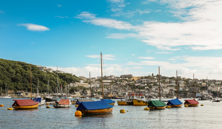 FOWEY, ENGLAND - July 20, 2018: picturesque Fowey harbour with moored boats in summer.