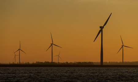 Aligned silhouetted windmills for renowable electric power Banco de Imagens