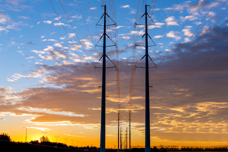 Electric power lines at sunrise with perspective and horizon against a colorful cloudy sky. Banco de Imagens