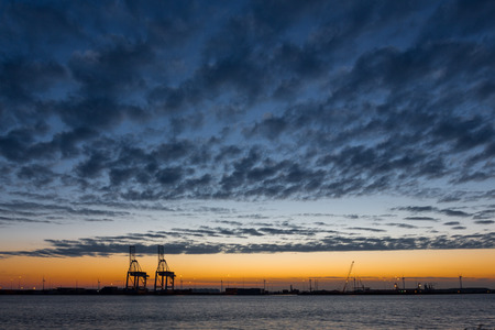 Industrial shipping port with cranes against a blue cloud scape in Amsterdam at sunset