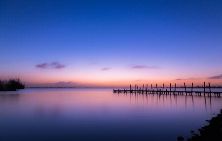 Beautiful winter blue and orange sunset at the Westeinderplassen Jetty at Aalsmeer near Amsterdam, The Netherlands. Long exposure.