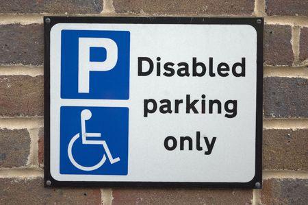 se�al parking: Un signo de aparcamiento minusv�lidos. En una pared de un aparcamiento en Inglaterra