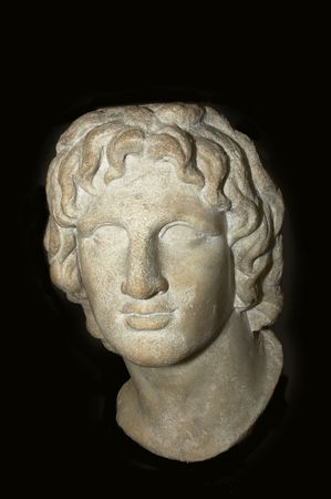 a greek statue of a head isolated on black photo
