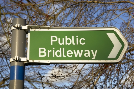 A public bridleway sign with trees in the background Stock Photo