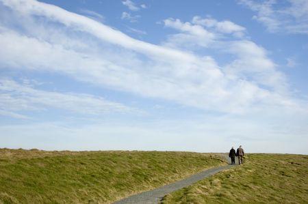 Un couple �g� de marche sur un chemin d'acc�s � un grand ciel