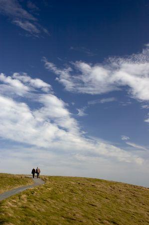Un couple �g� de marcher sur un chemin vers un grand ciel