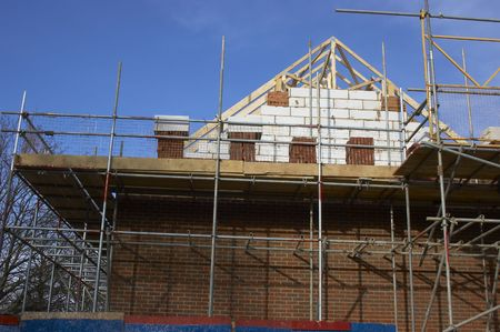 elevated walkway: Scaffolding around a new home in England Stock Photo