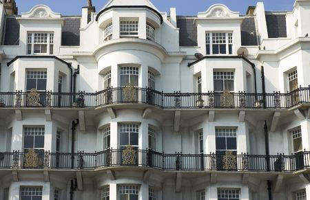 An old white victorian buildind with balconys