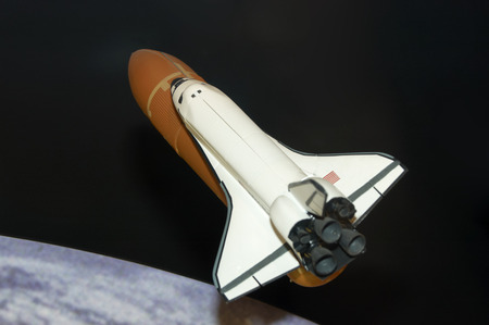 A modle of the space shuttle with the earth in the background