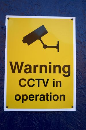 A cctv warning sign on a blue wall