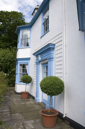 A nice blue and white house in the country Stock Photo