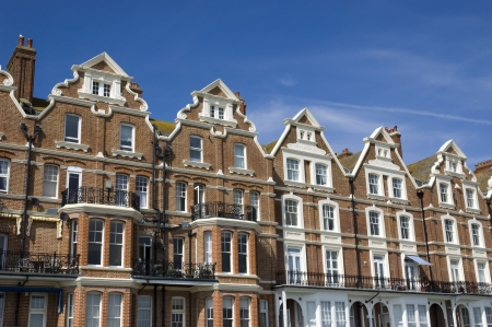 A row of victorian townhouses with a blue sky