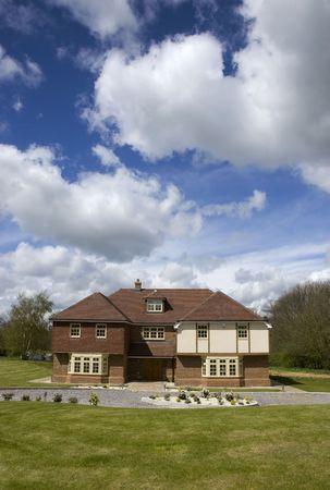 Une grande maison avec un ciel nuageux