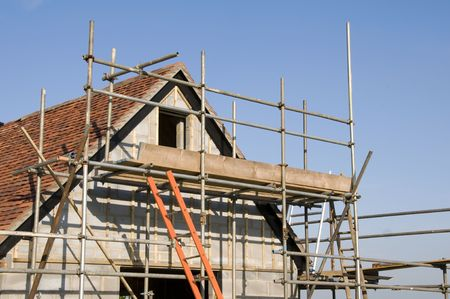 scaffold: Scaffolding around a new house in the countryside Stock Photo