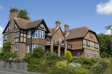 A large detached tudor style house with a blue sky