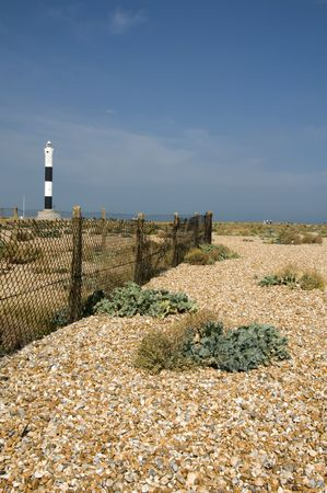The pebble  at Dungeness with the new lighthouse in the distance Stock Photo - 3694992