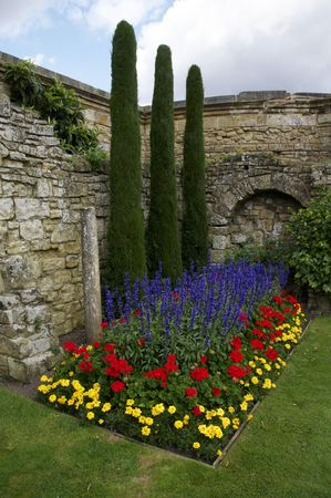A flower bed in a garden with purple flowers and a stone wall
