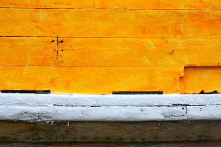 A close up veiw of the paint on a wooden boat