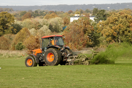 A view of an orange traacktor mowing a field Stock Photo
