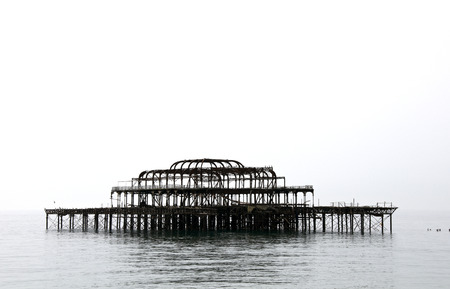The silhouette of a ruined pier in the fog.  Stock Photo