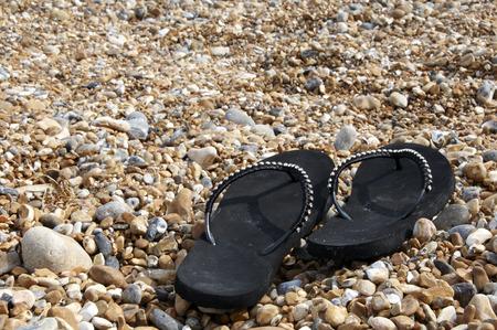 A pair of black flip-flops on a beach Stock Photo