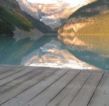 calm lake at the bottom of mountains with dock