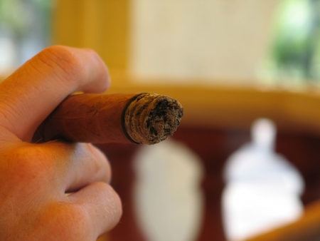 male hand holding a cigar photo