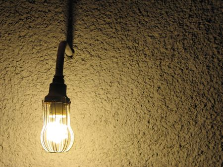 lit lightbulb in front of a wall
