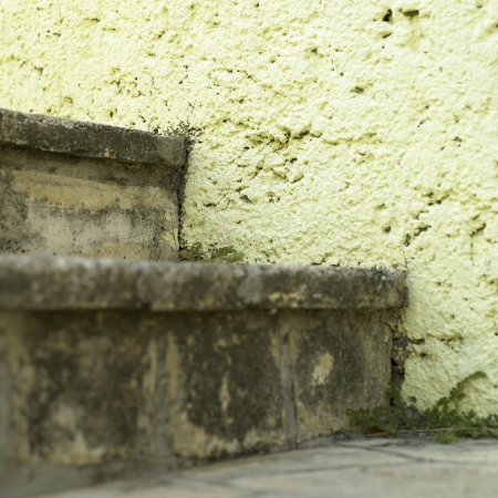 pitted: stone steps and yellow wall