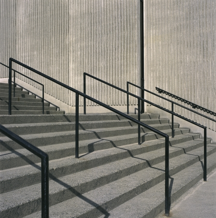 durable: Concrete steps and iron railings with groove concrete wall Stock Photo