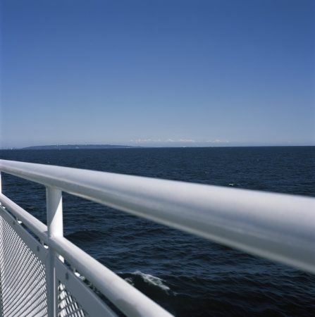 onboard: White metal railing against the blue ocean Stock Photo