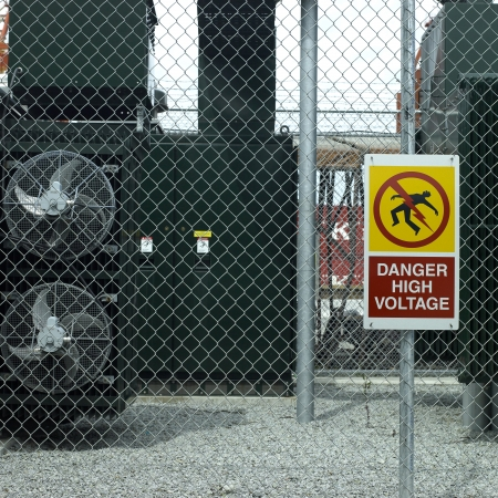 protective: Danger high voltage sign on a fence