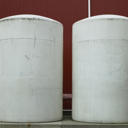 robustness: Large white barrels against red wall Stock Photo