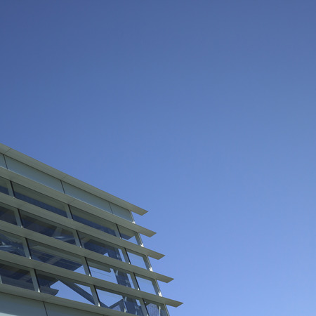 durable: Modern glass and metal building with blue sky Stock Photo