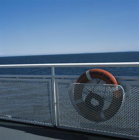 onboard: Oraange buoy on white railing of a boat