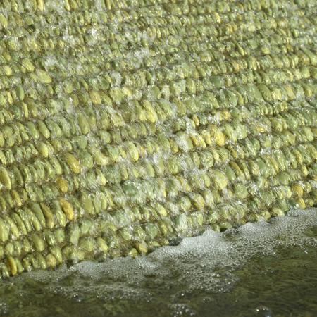Cascade of water over green pebbles photo