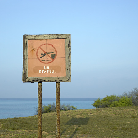 no diving sign: No diving sign on the edge of a cliff
