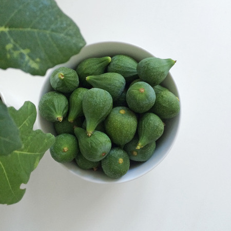 unripened: White bowl of green figs Stock Photo