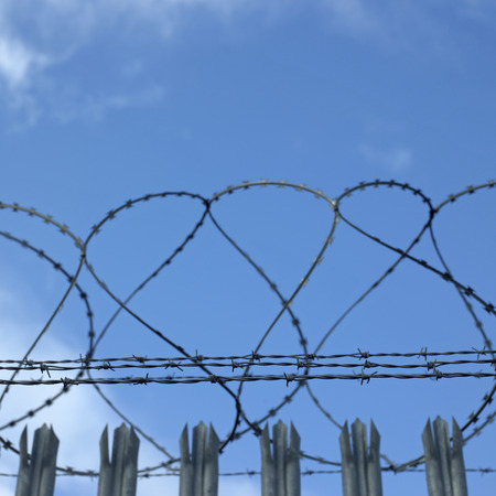 barbed wire fence: barbed wire fence and cloudy blue sky Stock Photo