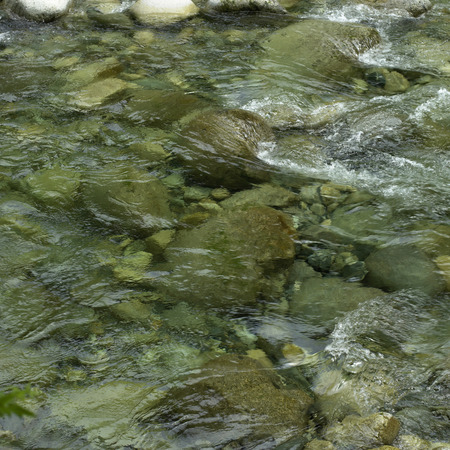 Close up of a river with clear water and stones photo