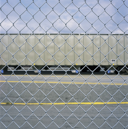 chain link fence: Looking at a train car through a chain link fence