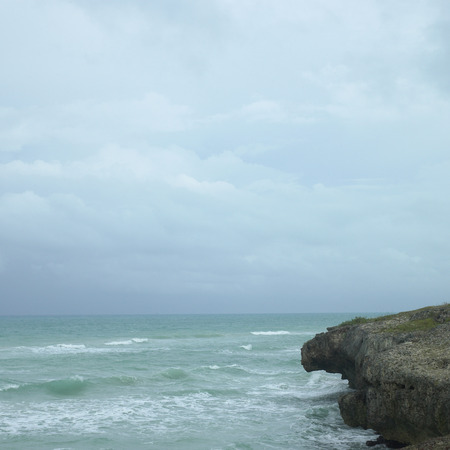 untroubled: Edge of a cliff with turquoise ocean Stock Photo