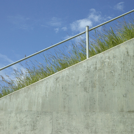 perpendicular: Industrial hand rail with grass and blue sky