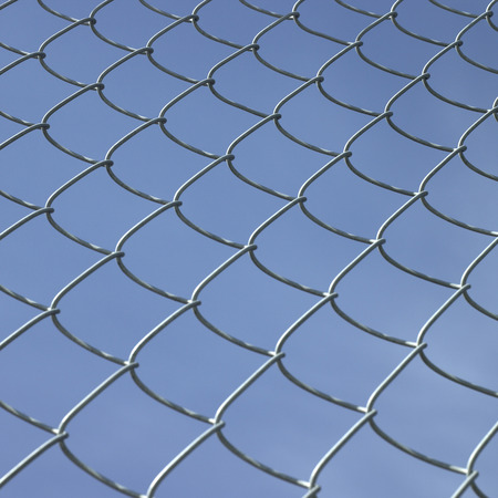 chain link fence: Chain link fence against blue sky