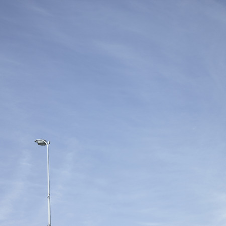 upright row: Streetlight towering up into a cloudy blue sky Stock Photo